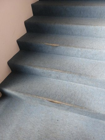 A section of worn carpet on the stairs - Image used for an incident investigation exercise in our IOSH Managing Safely online course